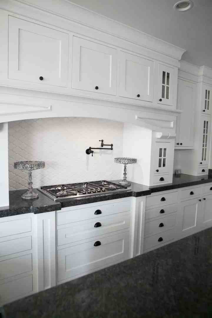White Kitchen Cabinets with gas cook top range.