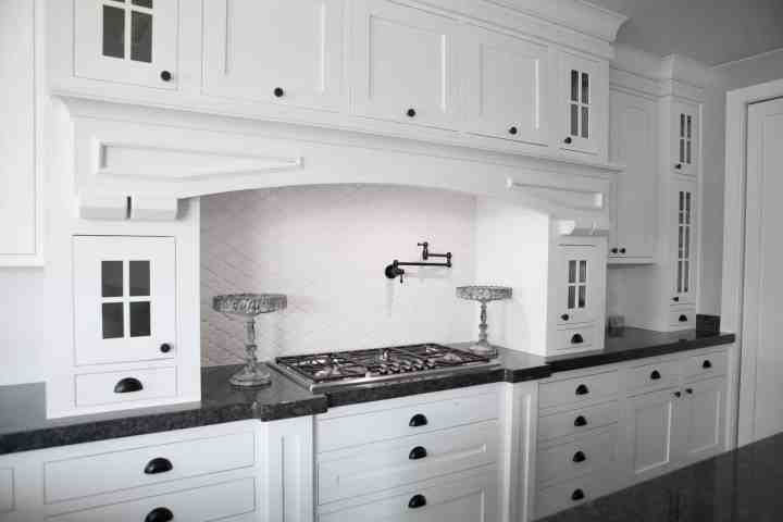 A large white kitchen with cabinets from floor to ceiling, with a large gas stove range with a white backsplash.