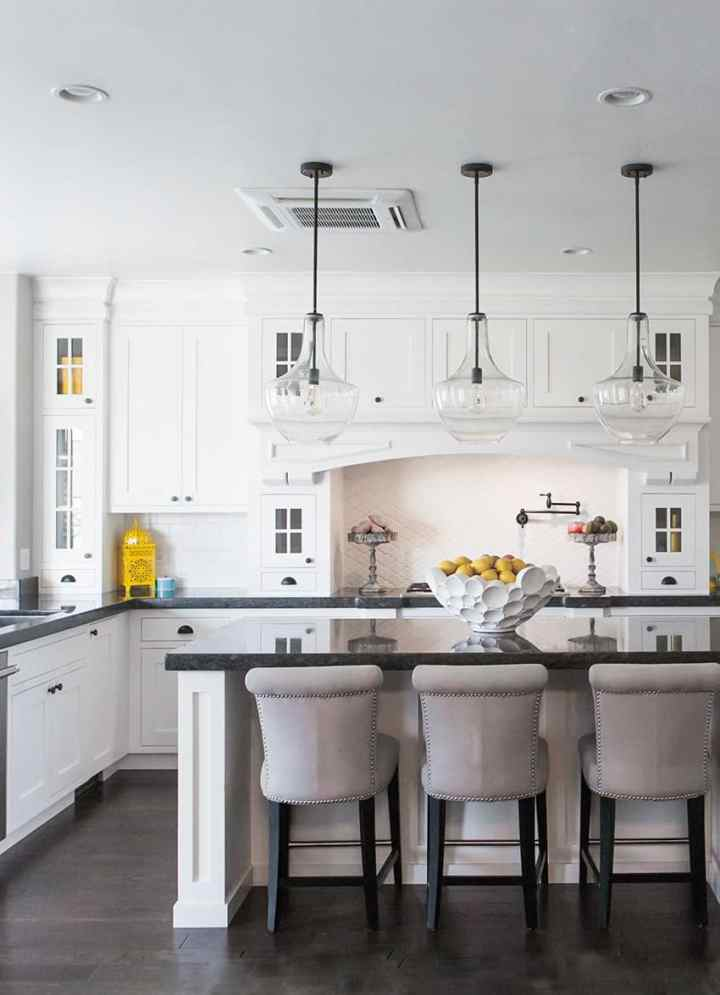 PIcture of a white kitchen, focusing on the kitchen island with 3 stools up to it.