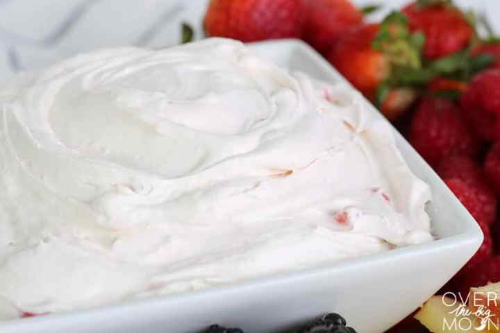 A bowl of strawberry fruit dip ready to serve with Strawberries and other fruit around the edges of the bow.