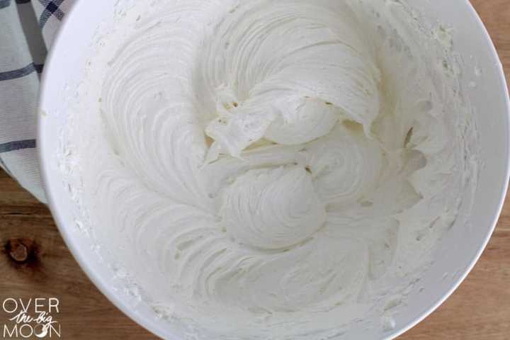 A bowl of cream cheese and cool whip mixed.