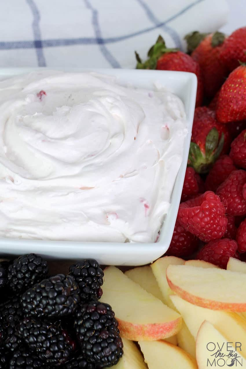 A bowl of Strawberry Fruit Dip surrounded by fruit.