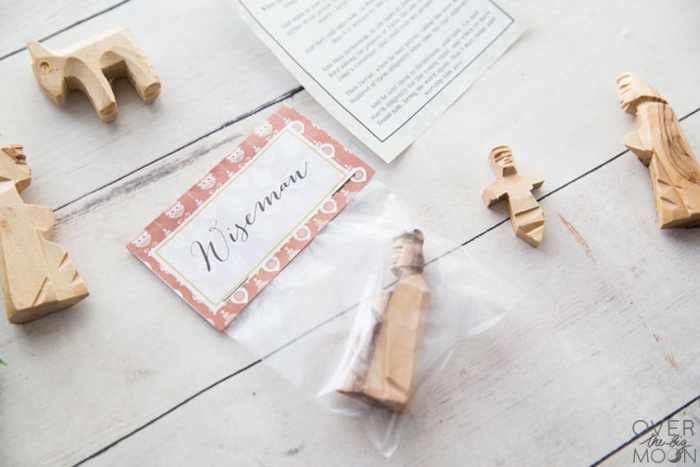 Wooden Nativity pieces laying on a white tabletop, with a Wiseman in a clear bag with a bag topper labeled Wiseman and a scripture.