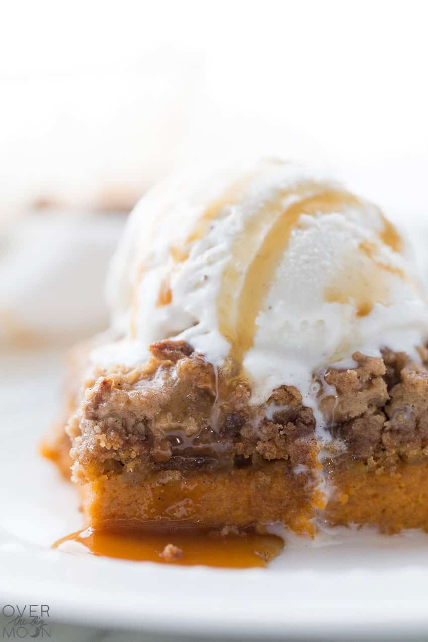 A piece of Pumpkin Dump Cake, topped with vanilla icecream and caramel sauce.