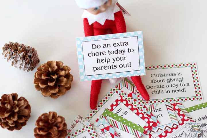 The Elf on the Shelf sitting in a pile of printed and cut Good Deed Cards