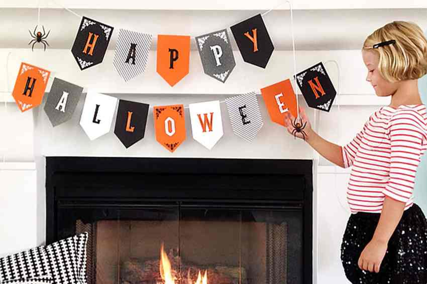 Happy Halloween Carnival Themed Banner - Grey, Black, Orange and White Banner hanging from a white fireplace, with a little girl standing to the right of it.