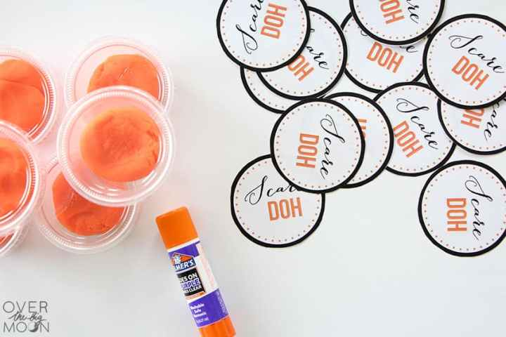 Cut out Scare Doh Circle Tags, next to containers of orange play doh and a glue stick.