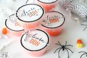 A stack of clear containers filled with orange play doh, with Scare Doh printable tags and a black and white twine tied around each container. Around the containers there are plastic black spiders and candy corns.