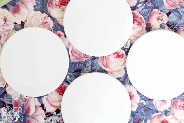 4 blank white coasters, sitting on a piece of floral Infusible Ink.