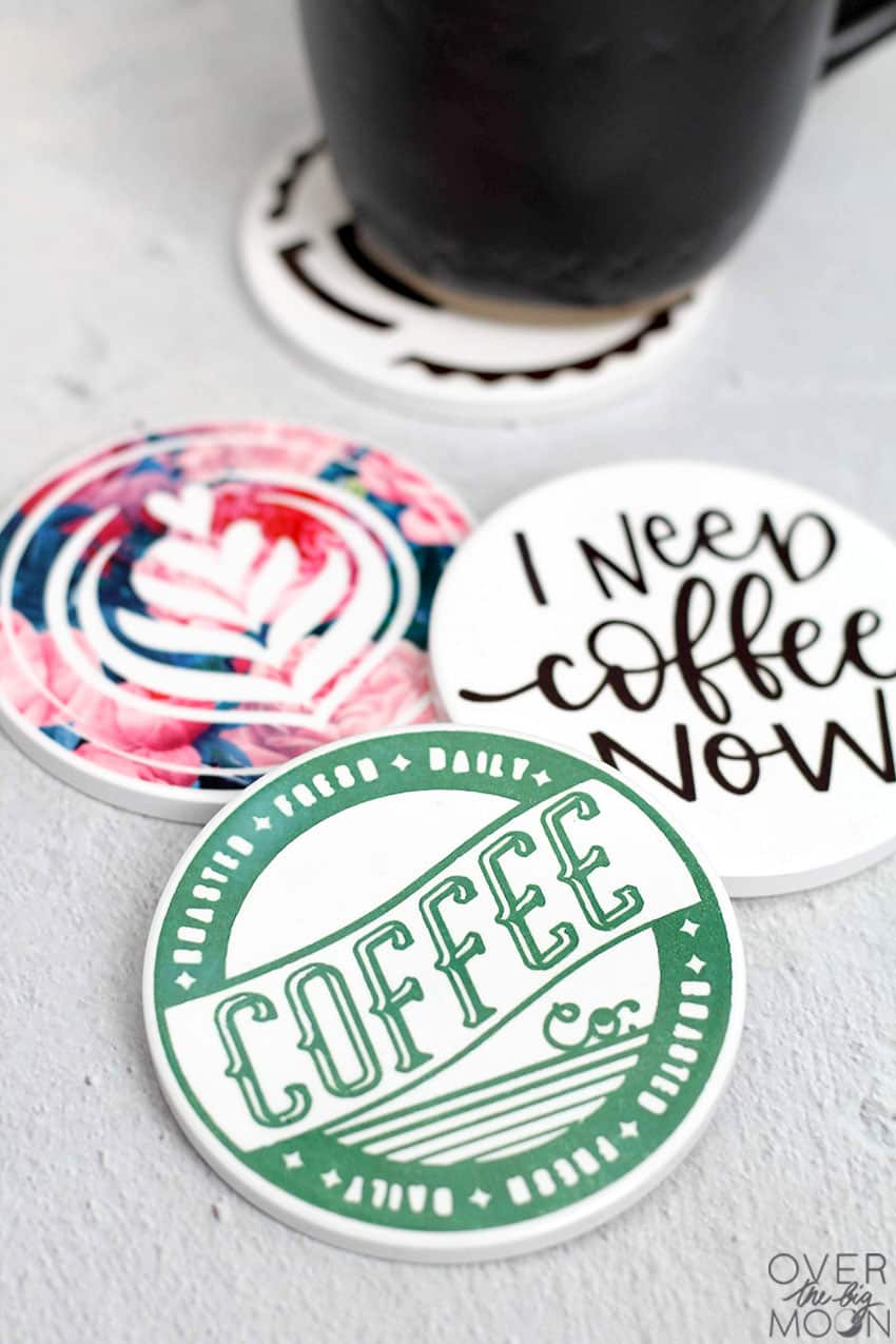 3 Coffee themed drink coasters with a black mug in the background on a 4th coaster.
