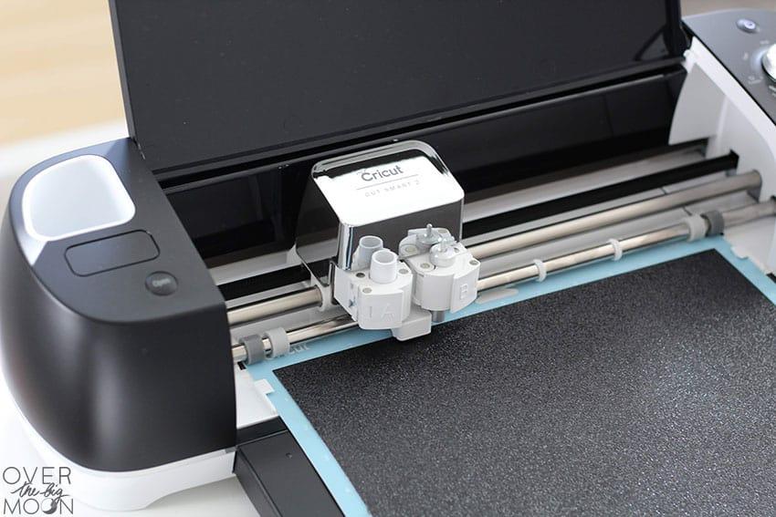 A Black Cricut Explore Air 2 machine - cutting Glitter Cardstock.