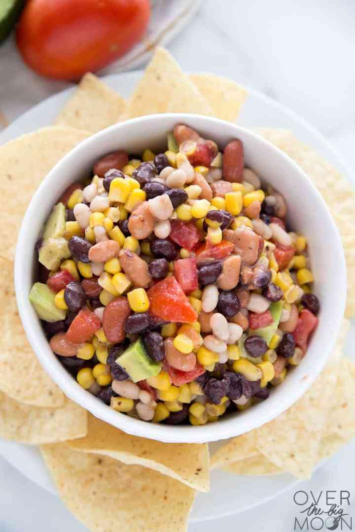 A Bean Chip Dip with 4 types of beans, corn, tomatoes, avocado and Italian dressing.