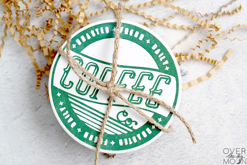 A stack of coasters that are Coffee themed, with a piece of twine wrapped around them.