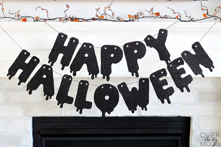 Happy Halloween banner hung on a fireplace mantel.