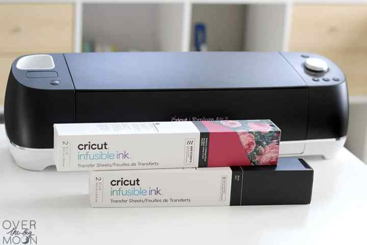 A Black Cricut Explore Air 2, with 2 boxes of Infusible Ink in front of it.
