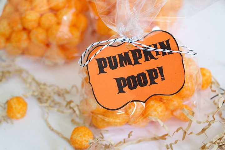 A bag of Cheetos Balls with a tag on the bag that reads Pumpkin Poop. In the background you can see additional bags being put together.