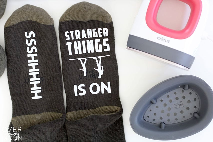 "A set of socks that read ""Ssshhhhh"" and ""Stranger Things is On"". The EasyPress Mini is laying to the side."