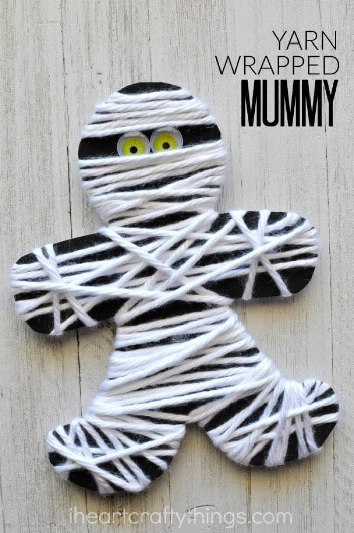 A cut out black mummy from cardstock, wrapped in white yarn with eyes poking out from the yarn.