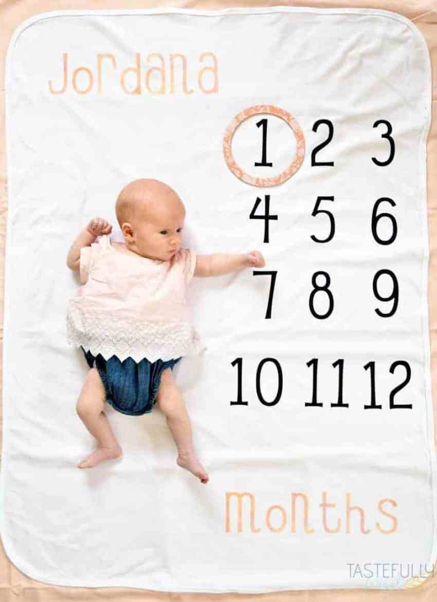 A blanket with the numbers 1 through 12 and a baby laying next to them.