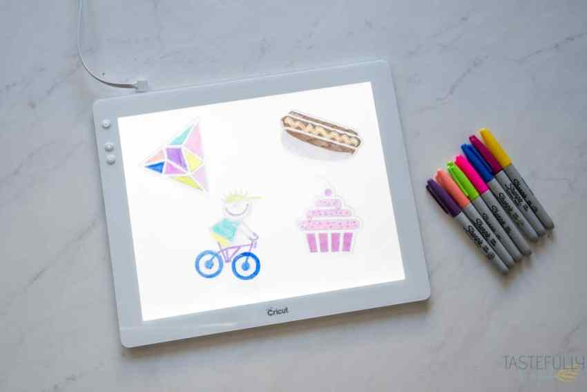 The Cricut BrightPad with 4 Shrinky Dink kids crafts on it, with a pile of Sharpie Markers to the side.