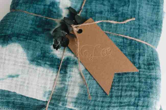 Engraved chipboard tag attached to a swaddle with twine.