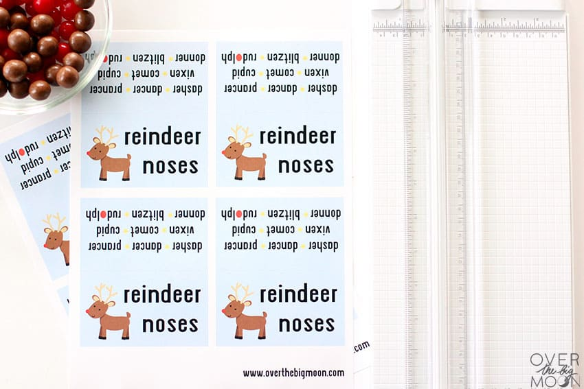 The printed Reindeer Noses Bag Toppers sitting next to a paper cutter and score board.
