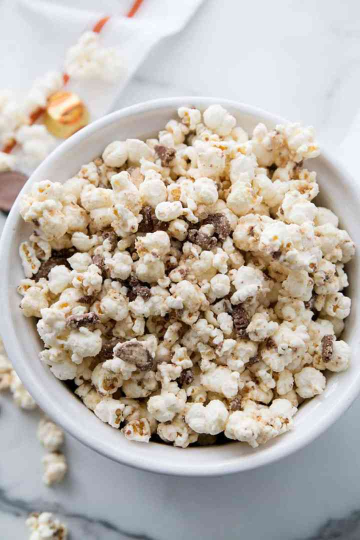A bowl of White Almond Bark Peanut Butter Cup Popcorn in a white bowl!