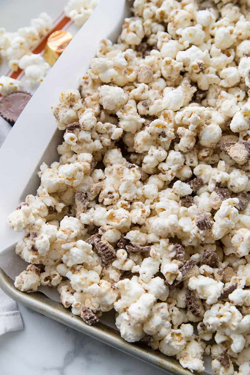 White Chocolate Peanut Butter Cup Popcorn spread out on a sheet pan to set.