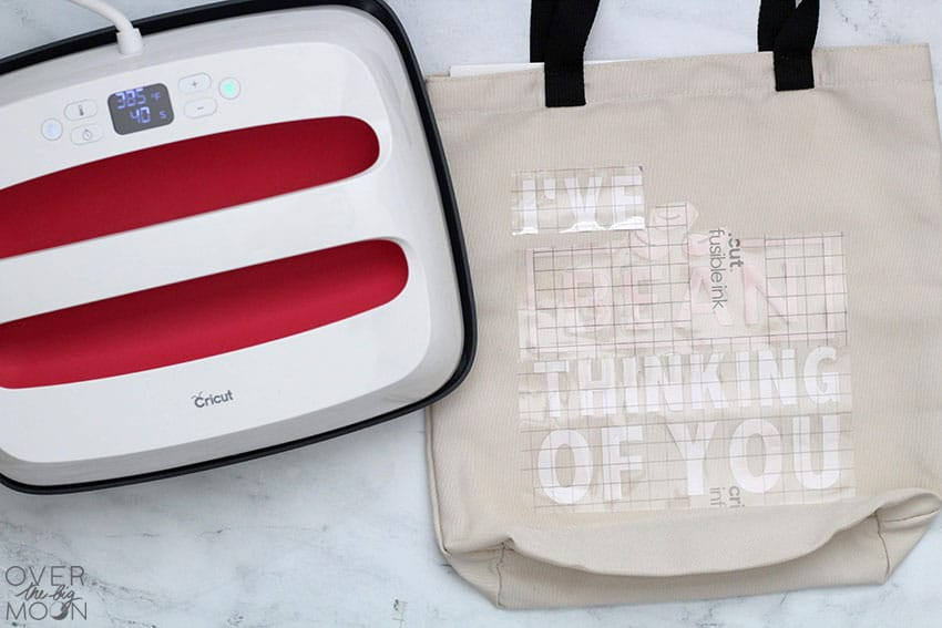 On the left is a 12x10 EasyPress 2 and to the right of it is a Infusible Ink Tote Bag with a word design placed on it, ready for heat!