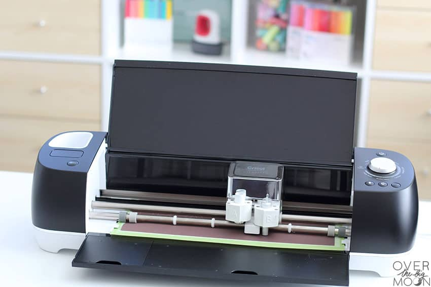 A black Cricut Explore Air 2 cutting black Infusible Ink with a craft storage shelf in the background.