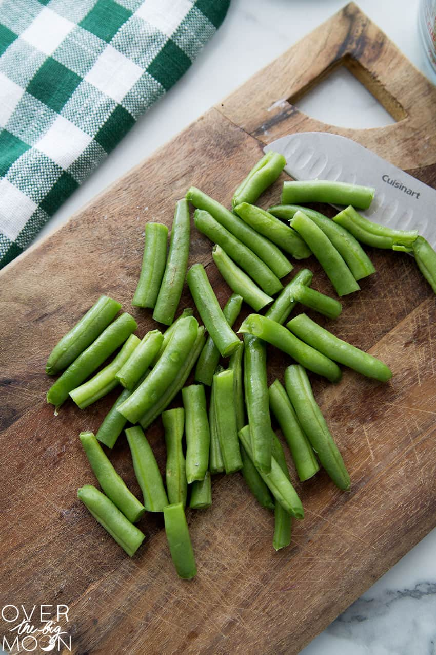 A cutting board with cut green beans on it.