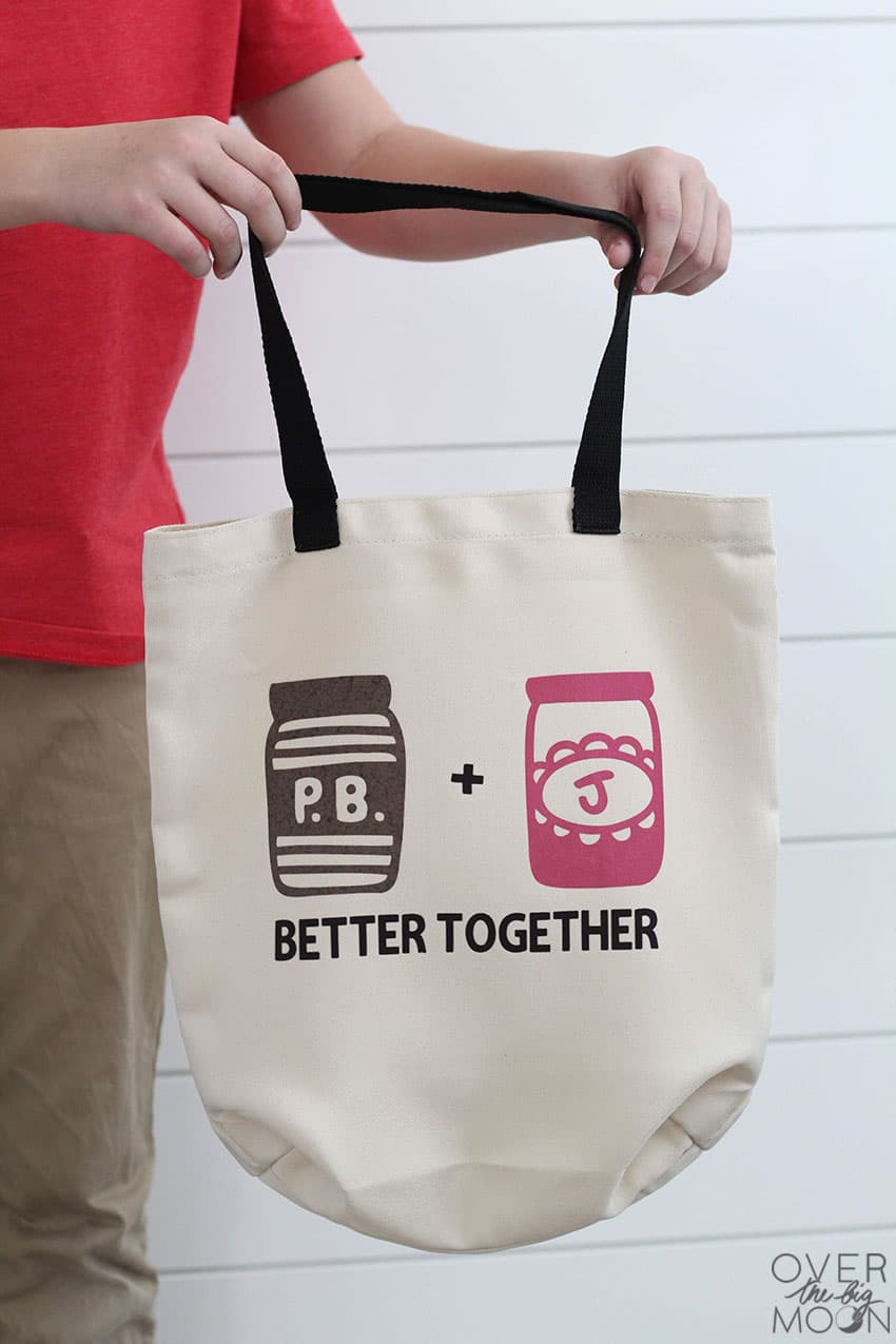 "A grocery tote bag that has a Peanut Butter Jar and Jelly Jar on it that says ""Better Together!"""