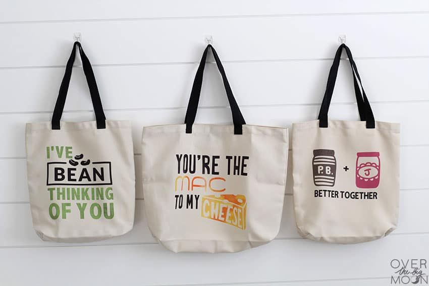 "3 tote bags hanging on the wall with fun food puns. One says ""I've BEAN thinking of you"", next one says ""You're the MAC to my CHEESE"" and the last one is a bottle of PB and Jelly can it says ""Better Together"" under it."