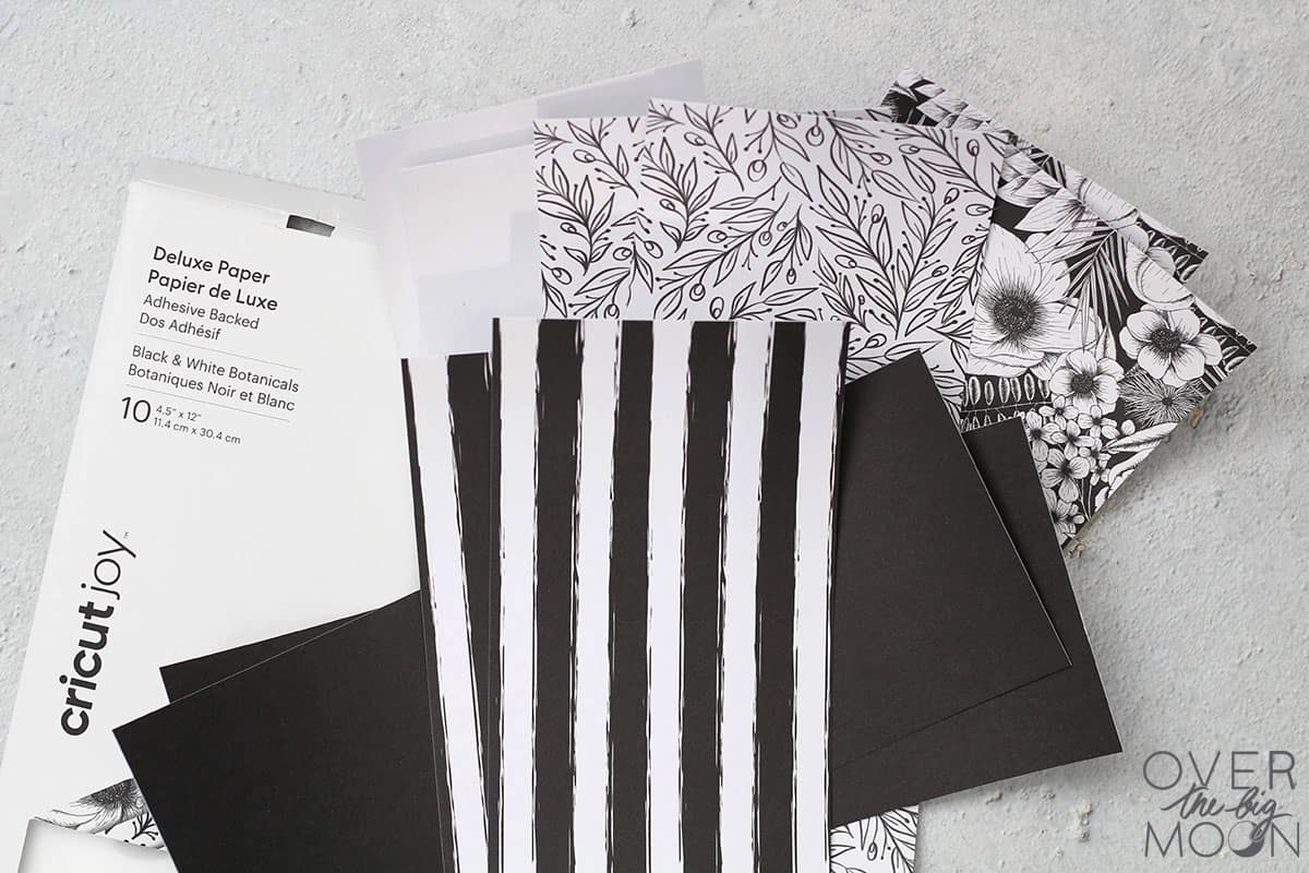 Black and White Adhesive Backed Paper scattered in a pile.