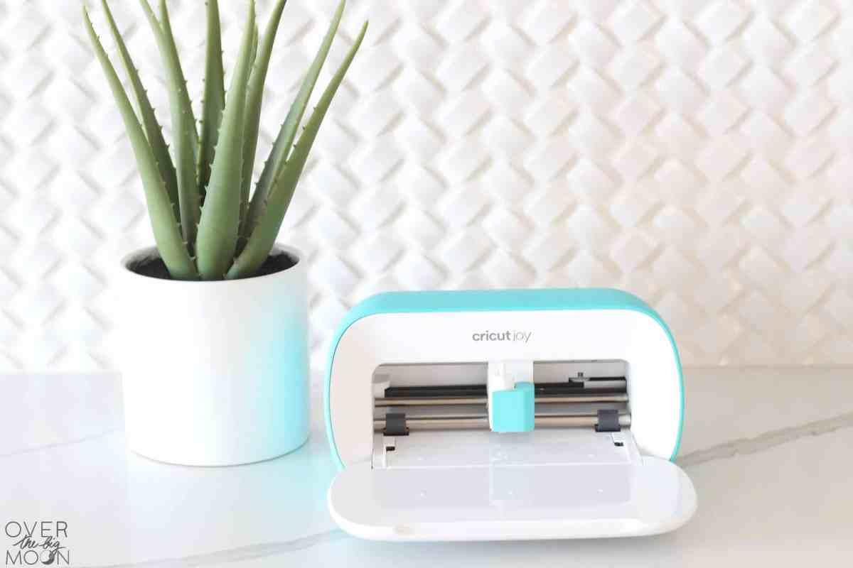 Cricut Joy machine open on white countertop with an aloe plant next to the machine.