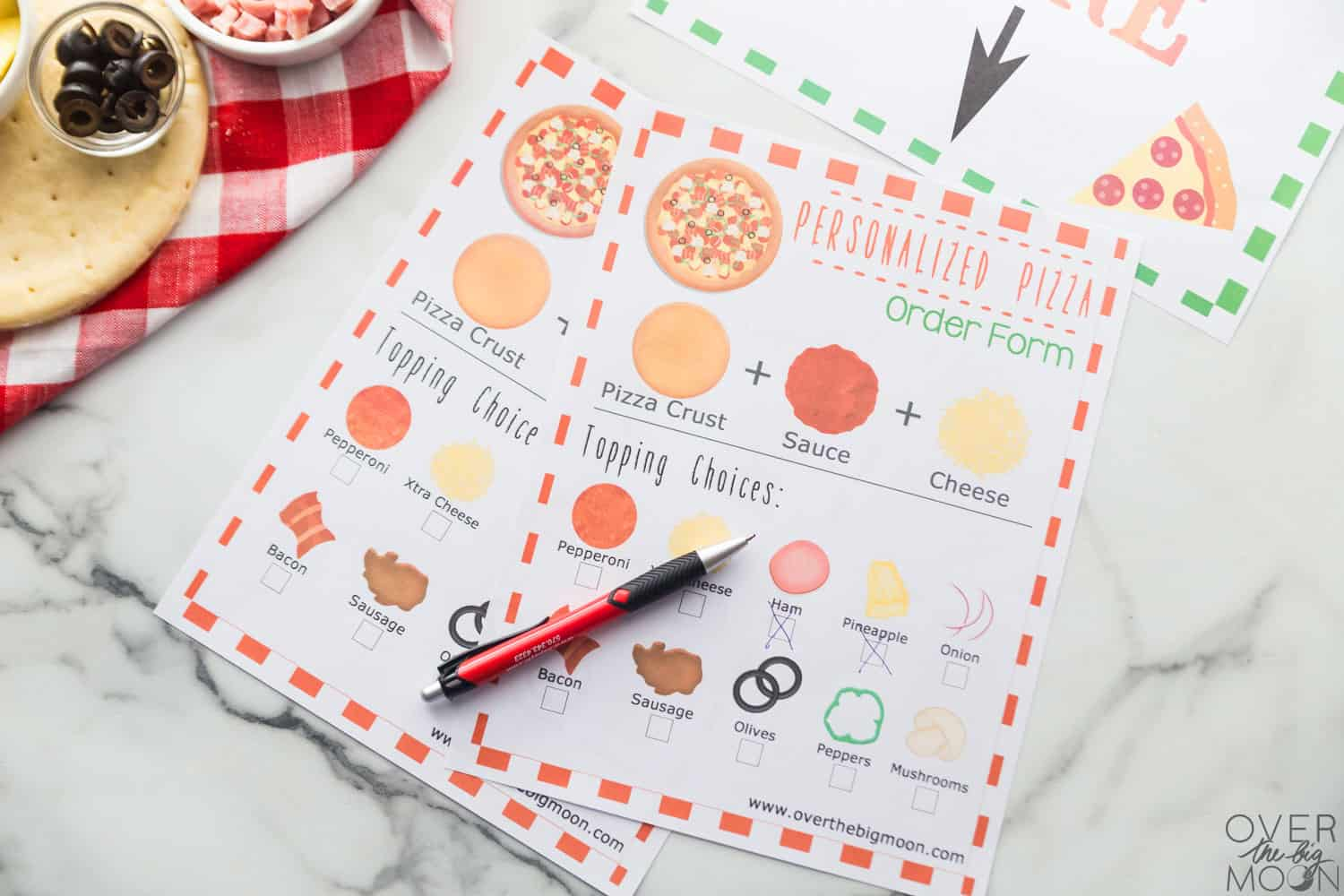 Printed Pizza order forms laying on a counter top with a pen and pizza supplies around them.