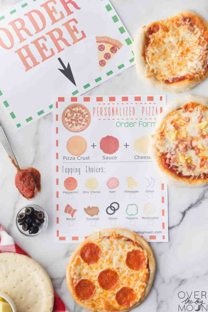 "A printered ""Order Here"" sign and a printable pizza order form below it on a table. With pizza supplies and cooked mini pizzas around them."