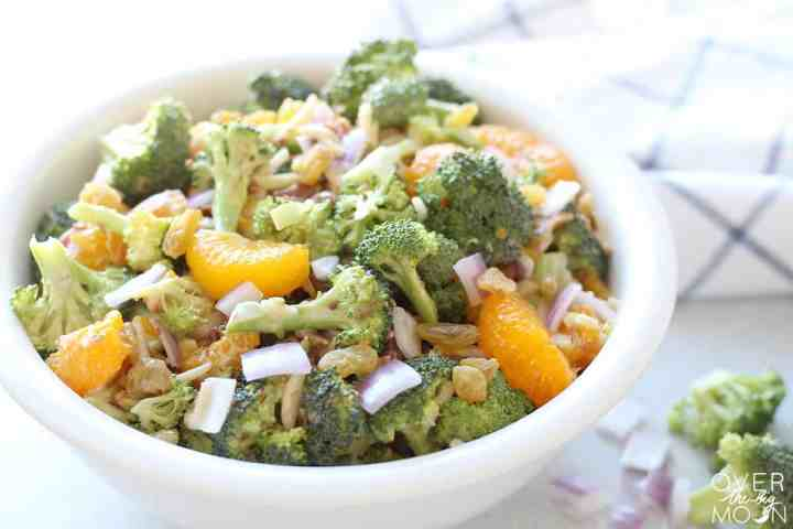 A white bowl of broccoli salad with broccoli, mandarin oranges, golden raisins, bacon, slivered almonds.