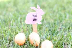 A pink bunny Easter Egg Hunt Printable Sign in the ground.