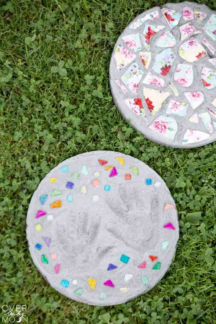 Two garden stones on grass. One with handprints and gems in it and the other with pieces of china.