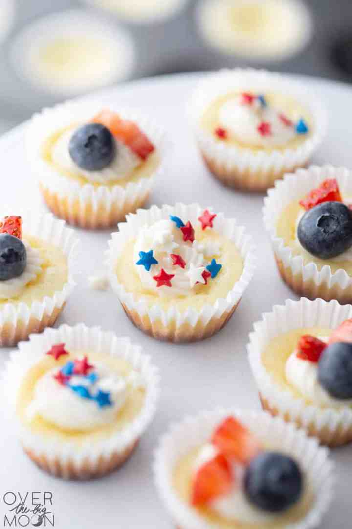 4th of July Mini Cheesecakes. Some with red white and blue sprinkles and others with small fruit on it.