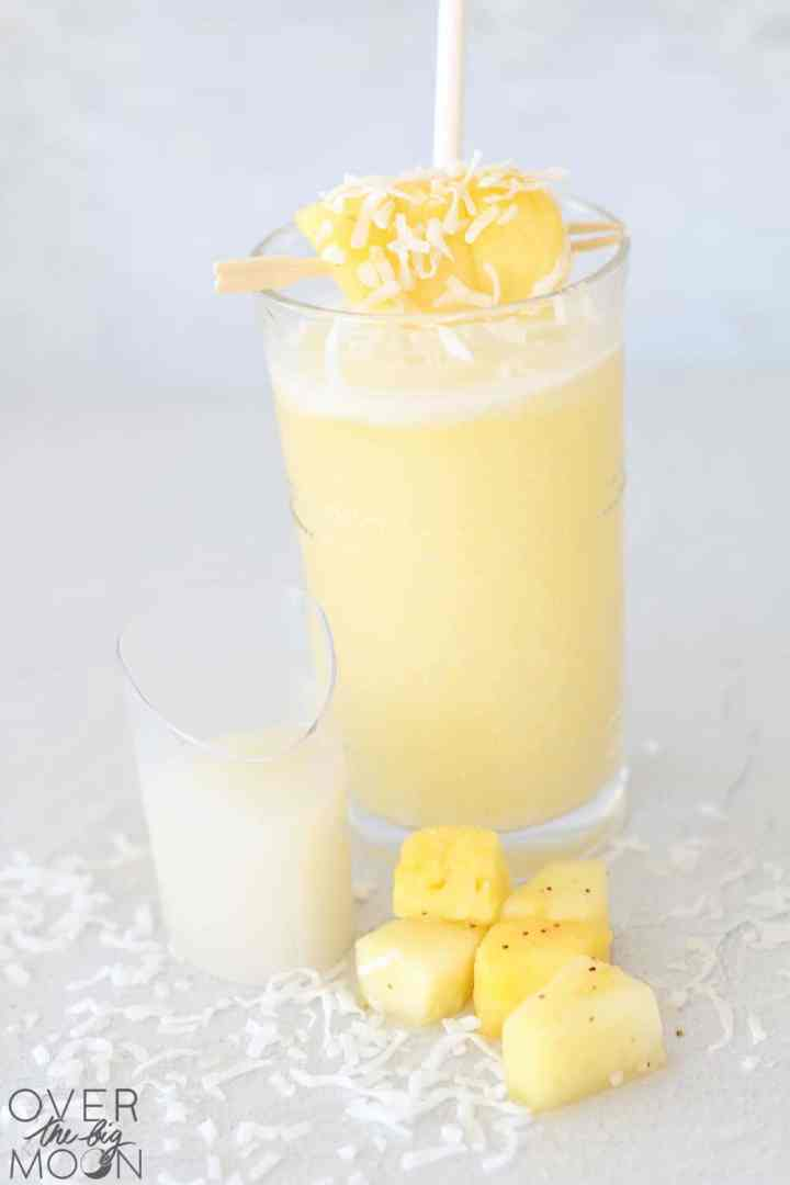A glass of Pina Colada drink with chunks of pineapple and coconut flakes around the base of the glass. Also a small clear container of cream of coconut.