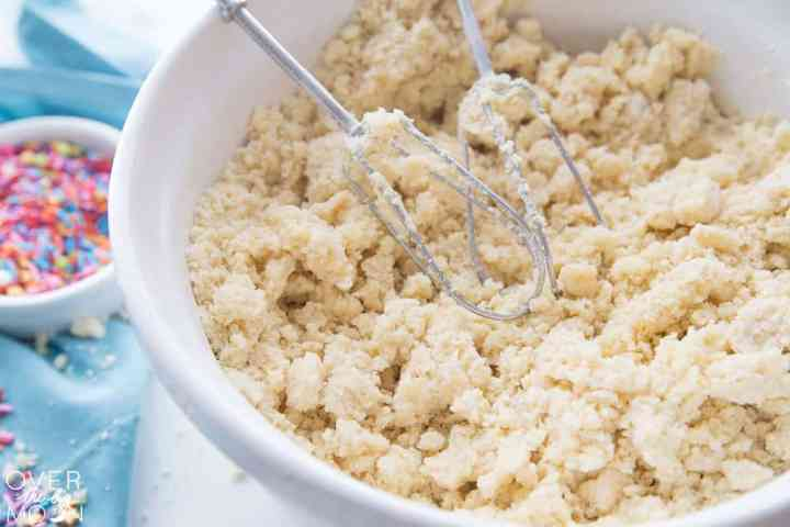 A white bowl filled with a cookie mixture in it and two beaters sitting on top of the mixture.