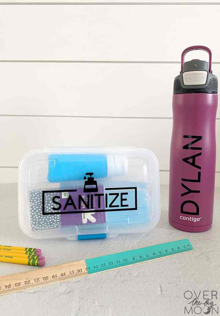 Kids sanitation kit made and purple tumbler next to pencils and a ruler.