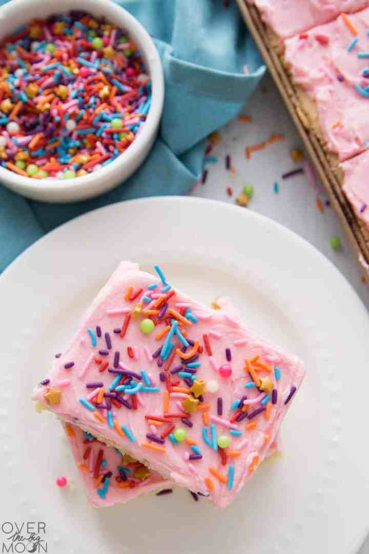 Two sugar cookie bars with pink frosting and sprinkles stacked on a white plate. In the background is a small bowl of sprinkles and the pan of sugar cookie bars.