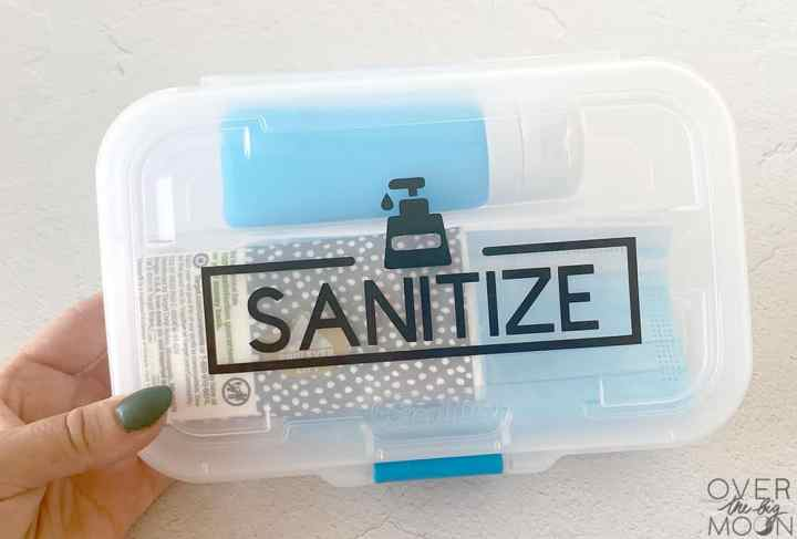 Sanitize vinyl sticker applied to the top of a clear container with supplies inside.