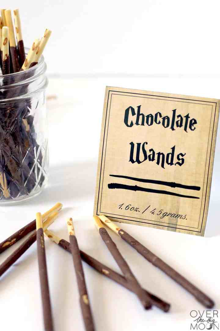 Some chocolate wafer sticks in a clear jar and laying on a white table. Next to them is a candy label that says Chocolate Wands.