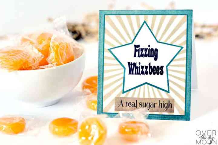 Butterscotch candies in a white bowl and on the table with a candy label that says Fizzing Whizzbees next to them.