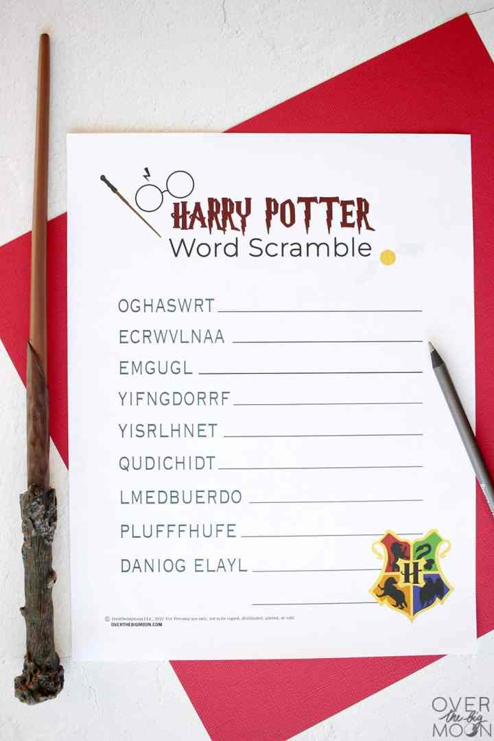 A Harry Potter Word Scramble Printable Game on a table on top of a red and yellow piece of cardstock. Sitting around the printable is a Harry Potter wand, glasses and a silver pencil.