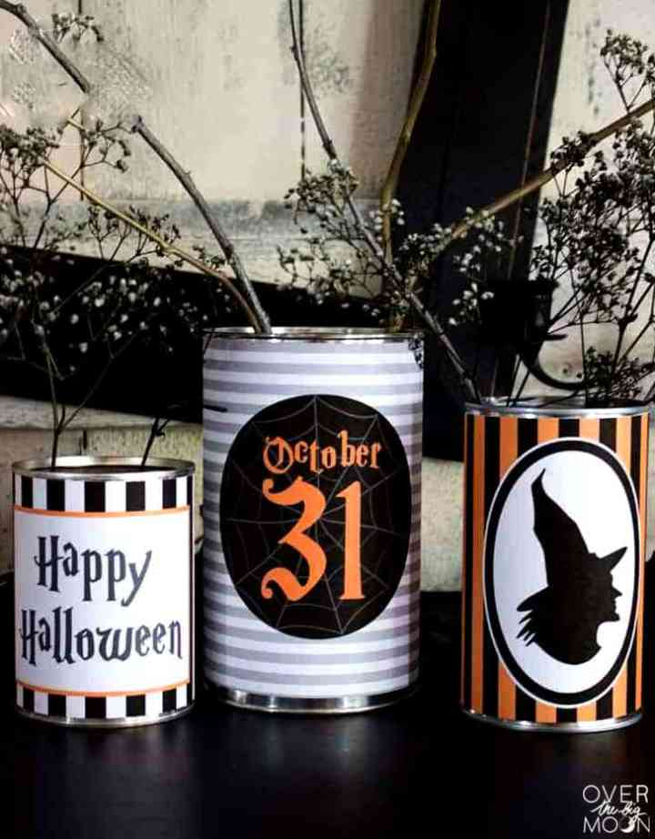 3 Tin Cans that are wrapped in Halloween tin can printables to create Halloween Decor. Spray painted babies breath is in the cans.